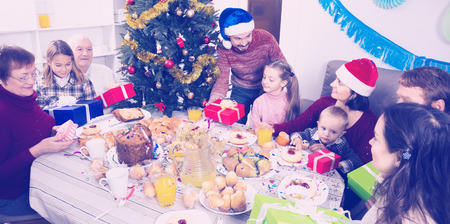 Happy family members presenting gifts during Christmas dinner Standard-Bild