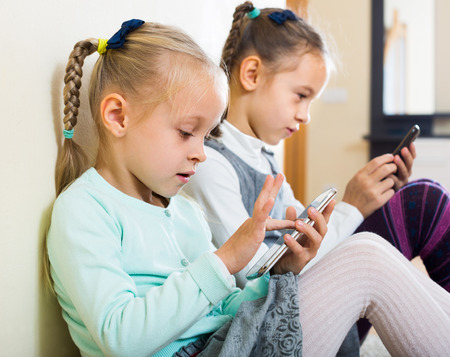 Two little girls 4s playing with smartphones at home Stock Photo