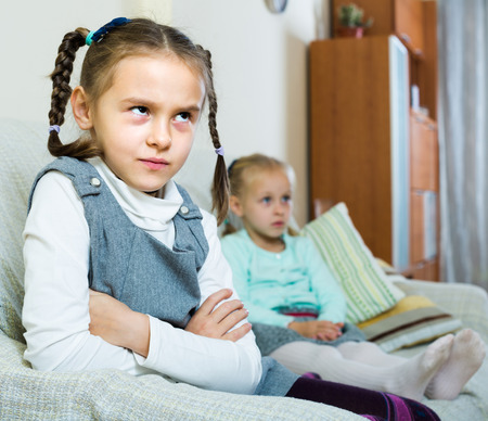 Offended girl sitting apart of little sister after argue at home