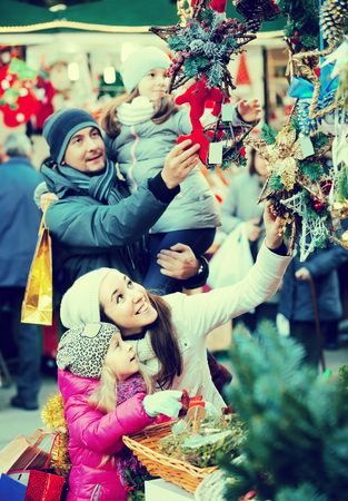 Happy young family with two little kids choosing X-mas decorations in market. Focus on woman