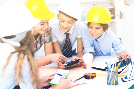 Group of children in helmet talking about building near laptop  Stock Photo