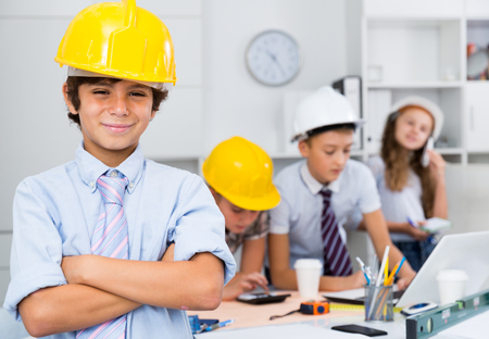 Teenager boy engineer and children with plan and notebook in the office