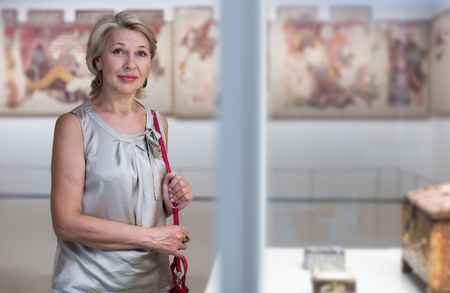 Mature woman standing near the ancient exhibit in art museum