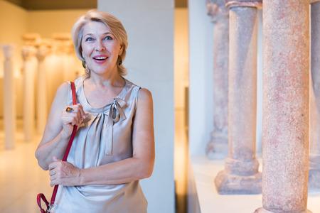 Mature female standing in art museum near the classical columns