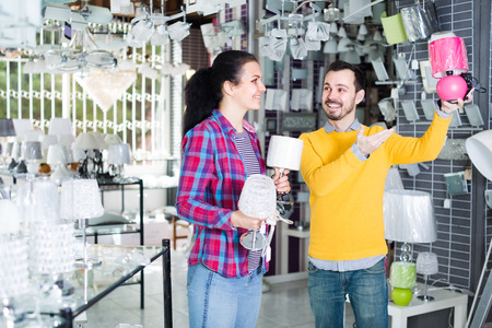 Family of two in shop of home appliances are choosing night lamp for home.