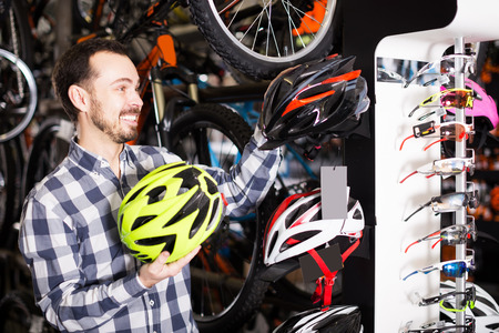 Young man decide on  helmet for cycling in a bike shop