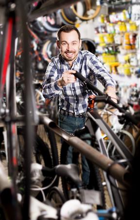 Cheerful man considers  bicycle handlebar in store when choosing bike