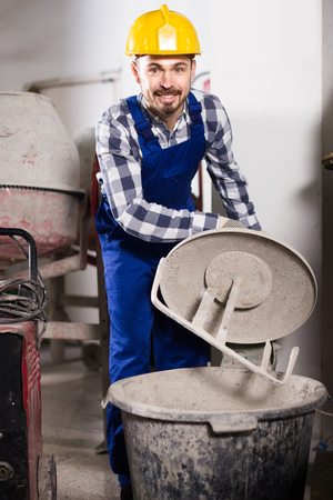 Smiling european working man practicing his skills with mixing unit at workshop