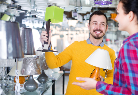 Positive man and girl in lighter shop choose stylish and modern lamp for house interior