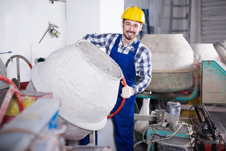 Young positive worker using concrete mixer for construction work at workshop  Stock Photo