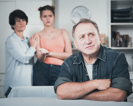 Upset father is sitting at the table and her family is sympathying with her at home.