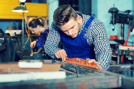 Adult man is working with level on his workplace in workshop