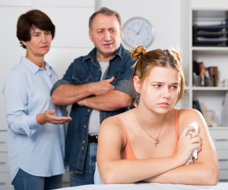 Parents are sympathying their sad daughter who is sitting at the table at home.