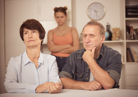 Upset female and her husband are sitting at the table and their daughter is sympathying with them at home. Stock Photo