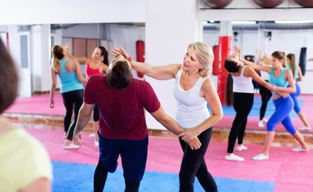 Glad cheerful  mature woman with her instructor are training self-defence moves in gym.