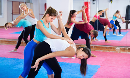 Glad cheerful positive women are doing self-defence moves in pairs in sporty gym.