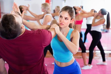 La hembra sonriente alegre contenta alegre está entrenando movimientos de autodefensa en pares con el instructor en gimnasio deportivo. Foto de archivo
