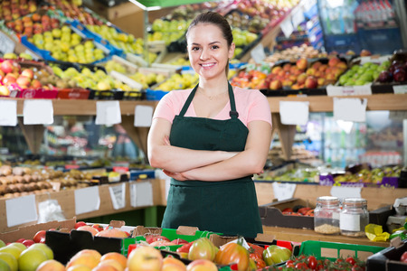 Portrait of young confident seller of vegetable store standing behind counter