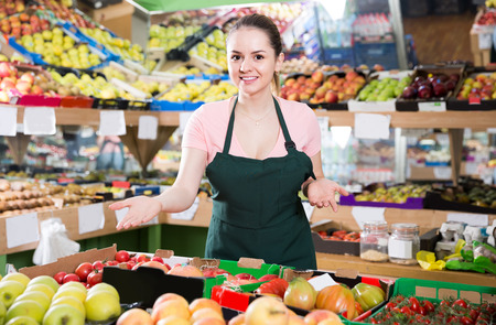 Friendly attractive italian salesgirl proposing fresh fruits and vegetables in supermarket  Stock Photo