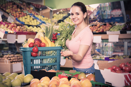 Young australian woman with basket with fresh greengrocery enjoying purchases in vegetable store