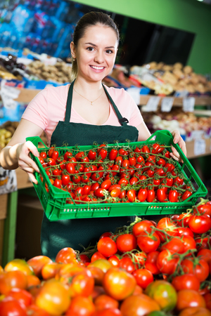 Friendly female grocery worker with plastic box of ripe red tomatoes Stock Photo