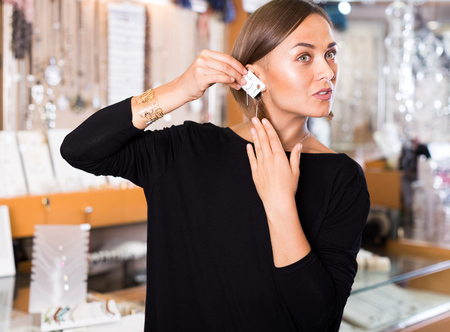 Adult buyer woman choosing a stylish earrings in a jewelry store