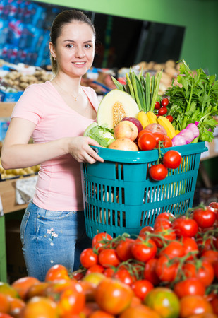 Young woman with basket with fresh greengrocery enjoying purchases in vegetable store