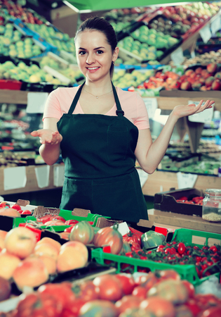 Friendly attractive spanish salesgirl proposing fresh fruits and vegetables in supermarket
