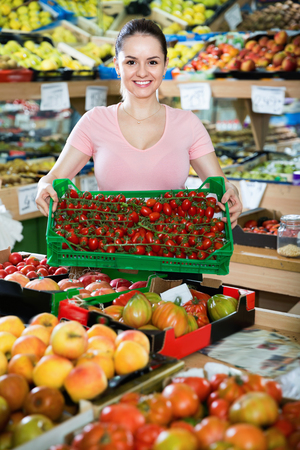 Friendly cheerful smiling attractive saleswoman with crate with tomatoes in supermarket Stock Photo