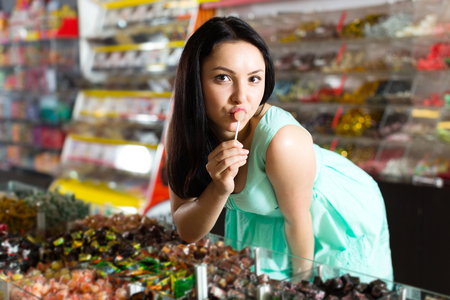 Happy adult girl posing to photographer with lollypop at candies store