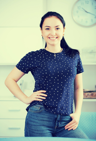 Young brown-eyed girl with smile standing with hand on waist