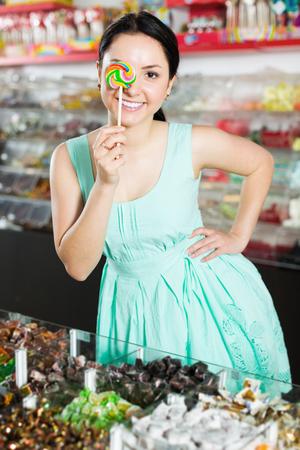 Portrait of young woman buying lollipop  at sweets shop Stock Photo