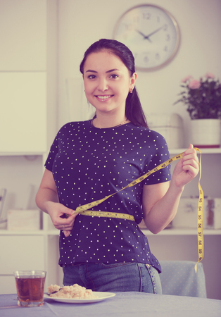Happy girl following diet and controlling waistline with measuring tape Reklamní fotografie