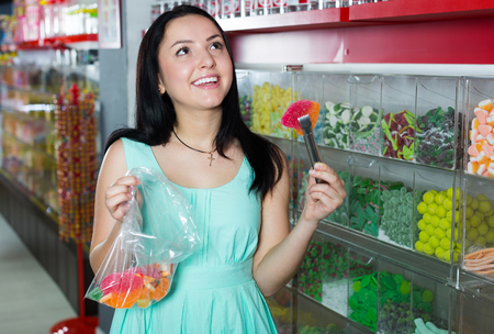 Happy girl in the store picks up candy in the bag Stock Photo