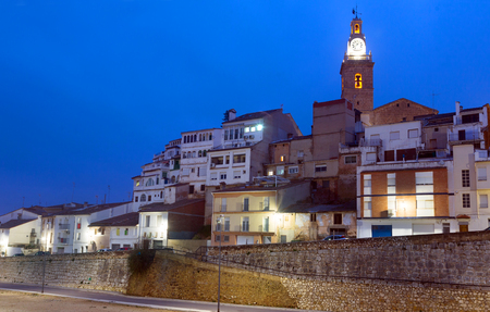 Illuminated residential quarter with church at dusk in Albaida