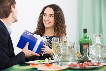 Woman presenting gift to man during romantic dinner Stock Photo