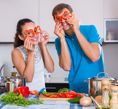Young family couple cooking vegetables inside