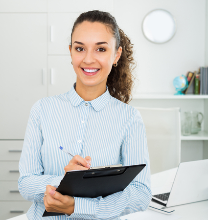 Positive business lady holding desk with documents in hands in office Stock Photo