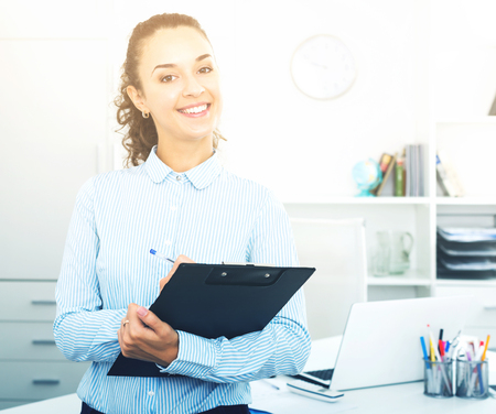 Attractive business woman with pad standing near office desk Foto de archivo