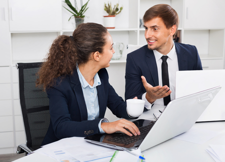 Two diligent glad smiling business male and female assistants wearing formalwear having work conversation in company office
