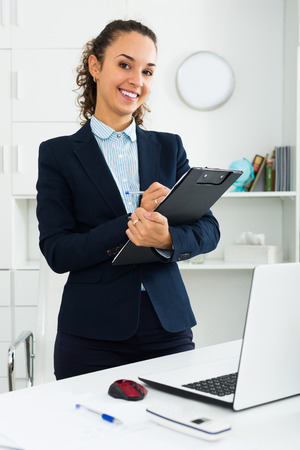 Positive and confident young woman holding documents in hands in office Stock Photo