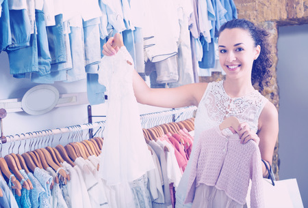 Young cheerful female choosing baby dress in kids apparel boutique