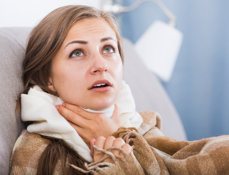Young woman catching cold, wrapping in blanket Banco de Imagens