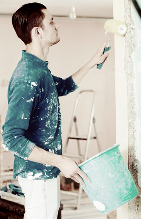 Handyman with priming roller renovating doorway in apartment and making prime coating  Stock Photo