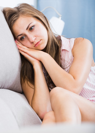 Young disappointed girl sitting on sofa at home