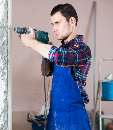 confident professional builder drilling hole in wall with perforator in a repairable room Stock Photo