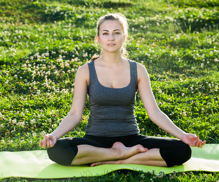 Young ukrainian female doing yoga poses on sunny morning in the green garden