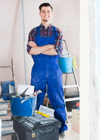Portrait of professional smiling builder standing in repairable room
