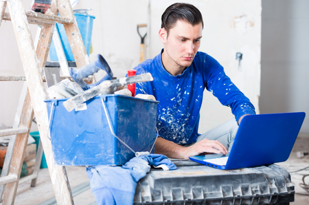 Young male contractor renovating house and working on laptop in repairable apartment Foto de archivo