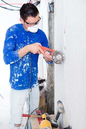 Professionality young male contractor using professional angle grinder for cutting wall
